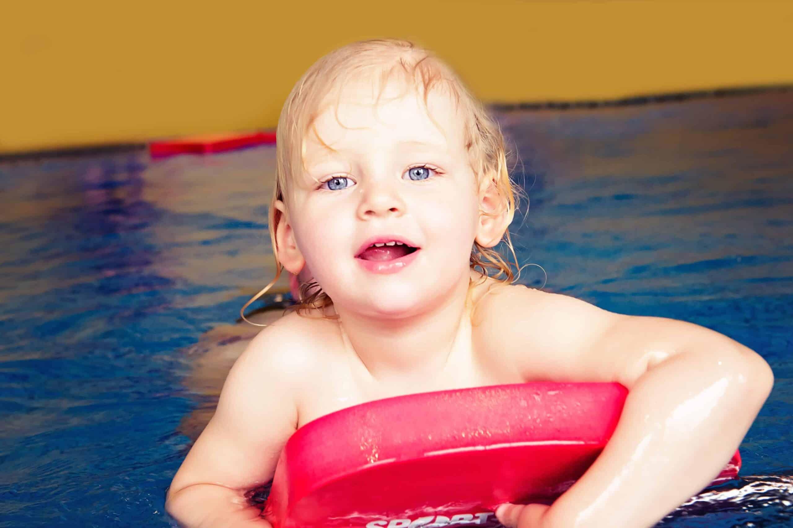 Kind im Wasser auf Schwimmbrett im Hallenbad Bremgarten