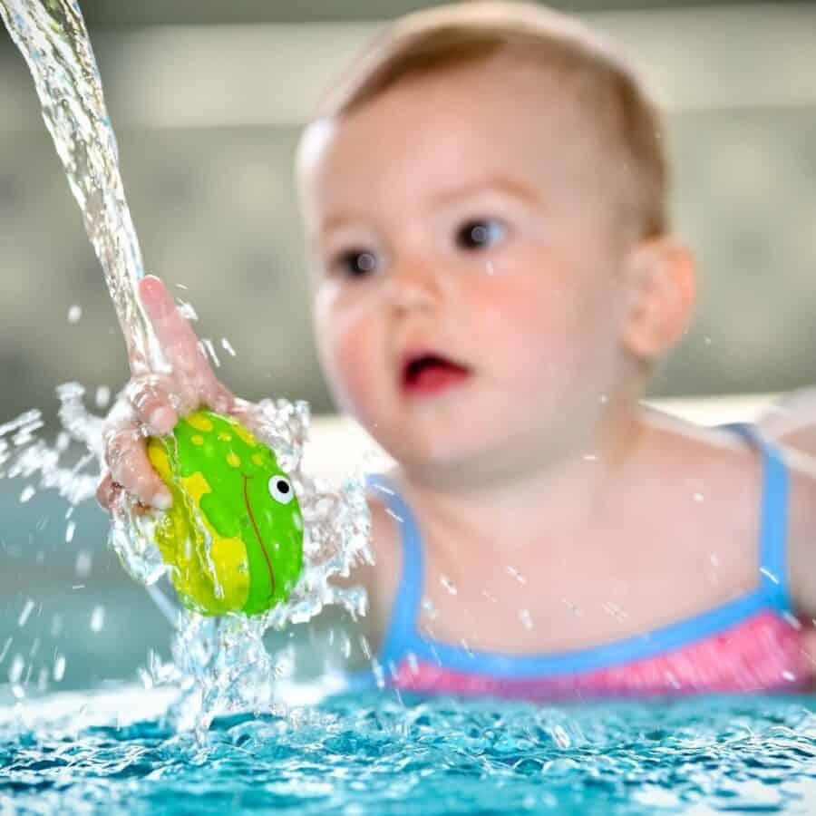 Baby im Wasser mit Frosch in der Hand