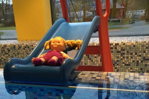 Puppe auf Rutschbahn im Babyschwimmkurs
